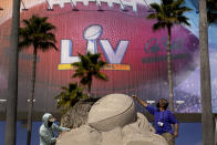 FILE - In this Feb. 4, 2021, file photo, workers sculpt the Lombardi Trophy out of sand outside of Raymond James Stadium ahead of Super Bowl 55 in Tampa, Fla. The city is hosting Sunday's Super Bowl football game between the Tampa Bay Buccaneers and the Kansas City Chiefs. (AP Photo/Charlie Riedel, File)