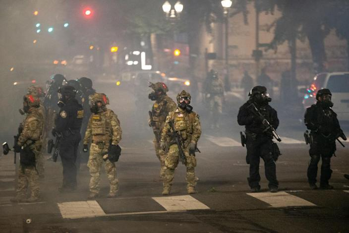 Federal police stand guard in Portland, Ore., on Tuesday night after pushing protesters away from the Mark O. Hatfield Courthouse. (Nathan Howard/Getty Images)