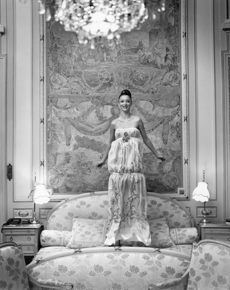 Model Audrey Marnay wearing a dévoré chiffon flower-print strapless dress by Emmanuel Ungaro Haute Couture, jumping on a bed in the Suite Duc de Windsor at the Hôtel Ritz, Paris; dress fabric by Etro