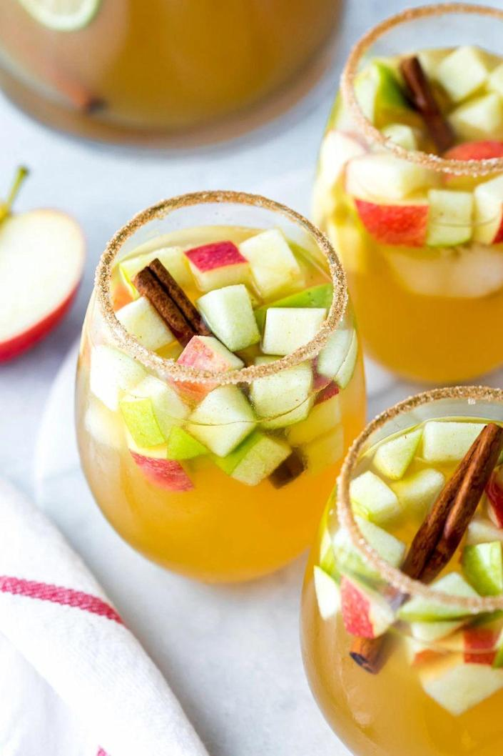 """<p>This fall-friendly version of white wine sangria is great for entertaining because you can prep it all in advance. Serve it in a pitcher and let your guests help themselves. </p><p><strong>Get the recipe at <a href=""""https://www.simplywhisked.com/apple-cider-sangria/"""" rel=""""nofollow noopener"""" target=""""_blank"""" data-ylk=""""slk:Simply Whisked"""" class=""""link rapid-noclick-resp"""">Simply Whisked</a>.</strong></p>"""
