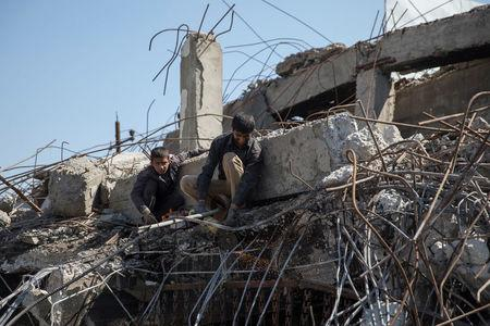 A man collects steel from a destroyed building in Mosul