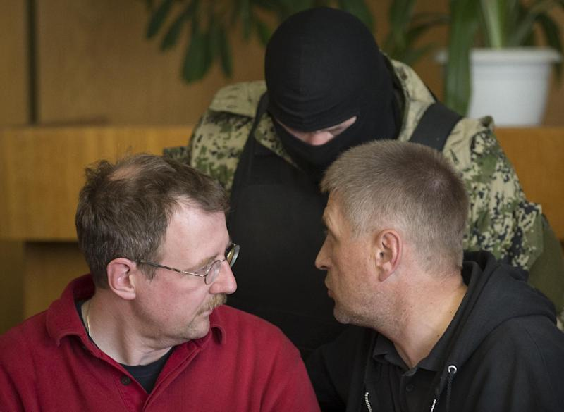 Vacheslav Ponomarev, the self-proclaimed mayor of Slovyansk, right, speaks to Axel Schneider of Germany, a foreign military observer being held by Ponomarev's group during a press conference in the city hall of Slovyansk, eastern Ukraine, Sunday, April 27, 2014. As Western governments vowed to impose more sanctions against Russia and its supporters in eastern Ukraine, a group of foreign military observers remained in captivity Sunday accused of being NATO spies by a pro-Russian insurgency. The German-led, eight-member team was traveling under the auspices of the Organization of Security and Cooperation in Europe when they were detained Friday. (AP Photo/Alexander Zemlianichenko)