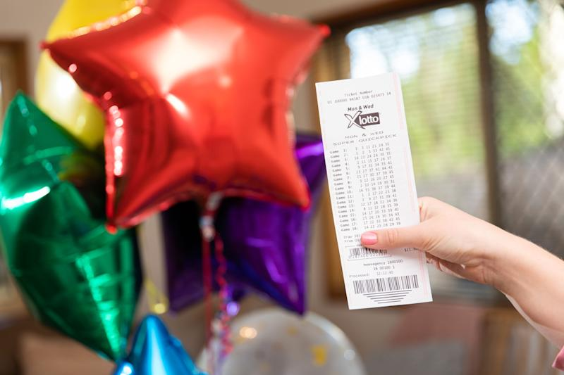 A woman holds a Monday & Wednesday X Lotto ticket in front of helium balloons.