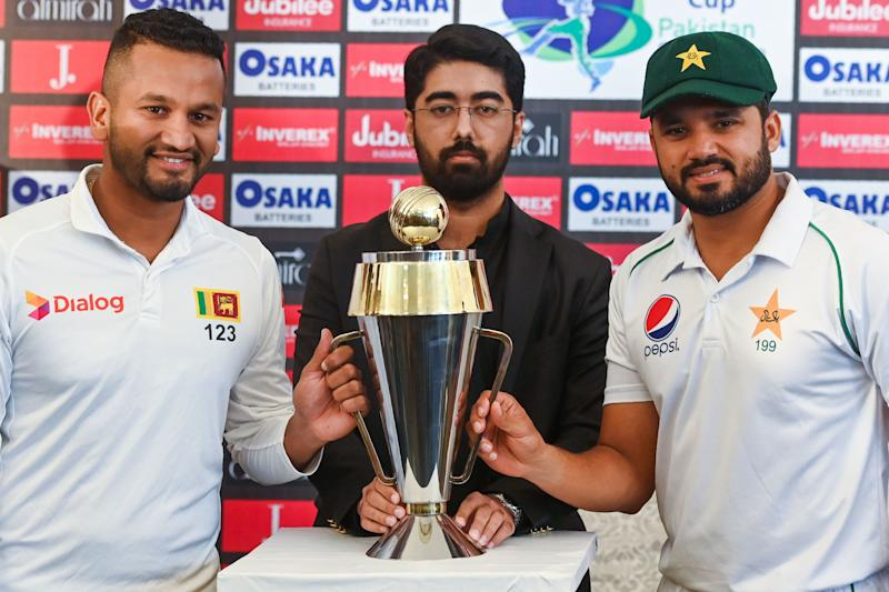 Pakistan's captain Azhar Ali (R) and his Sri Lankan counterpart Dimuth Karunaratne (L) pose for a photograph with Test series trophy at the Pindi Cricket Stadium ahead of the first Test cricket match between Pakistan and Sri Lanka in Rawalpindi on December 10, 2019. (Photo by Aamir QURESHI / AFP) (Photo by AAMIR QURESHI/AFP via Getty Images)