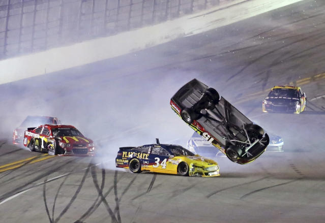 Clint Bowyer's car (15) becomes airborne after being hit by David Ragan (34) during the second of two NASCAR Sprint Cup series qualifying auto races at Daytona International Speedway in Daytona Beach, Fla., Thursday, Feb. 20, 2014. (AP Photo/David Graham)