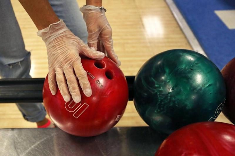 Melissa Cuadra, 41, wears gloves during a game at Bird Bowl Bowling Center on 9275 SW 40th St. in Westchester, Florida, as Miami-Dade County enters Phase 2 of reopening, Saturday, September 19, 2020.