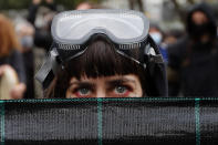 A protestor with a diving mask on her head, holds a banner during a protest in the capital Nicosia, on Saturday, Feb. 20, 2021, against the corruption within the country's politicians, as well as fatigue over restrictions to curb COVID-19 infections. The demonstration that drew an estimated 3,000 people came a week after police were strongly criticized for resorting to disproportionate force by using a water canon, stun grenades and pepper spray to disperse a crowd of a few hundred left-wing protesters voicing their opposition to corrupt politicians. (AP Photo/Petros Karadjias)