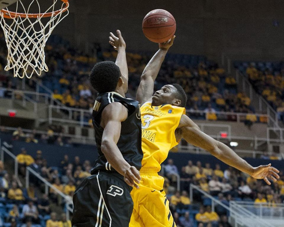 West Virginia's Juwan Staten, right, looks to dunk over a Purdue defender during the second half of an NCAA college basketball game on Sunday, Dec. 22, 2013, in Morgantown, W.Va. Purdue won 73-70. (AP Photo/Andrew Ferguson)