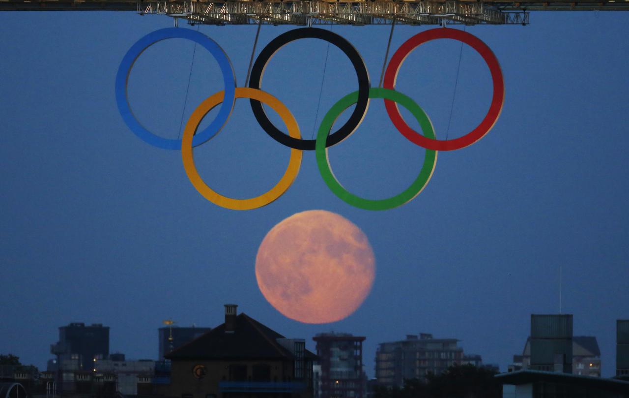 The full moon rises through the Olympic Rings hanging beneath Tower Bridge during the London 2012 Olympic Games August 3, 2012.  REUTERS/Luke MacGregor  (BRITAIN - Tags: SPORT OLYMPICS ENVIRONMENT CITYSPACE)