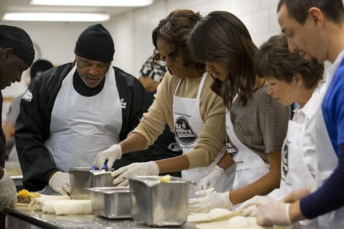 First lady Michelle Obama, center, with daughter Malia Obama and presidential adviser Valerie Jarrett, make burritos at DC Central Kitchen as part of a service project in honor of Martin Luther King, Jr. Day on Monday, Jan. 20, 2014, in Washington. Also helping were President Barack Obama and daughter Sasha Obama. (AP Photo/Jacquelyn Martin)
