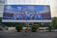 A city cyclist passes a billboard showing Mumbai's IPL team. Tens of millions of Indian cricket fans are playing fantasy games in a mushrooming billion-dollar industry which exploits a loophole in the country's strict gambling laws