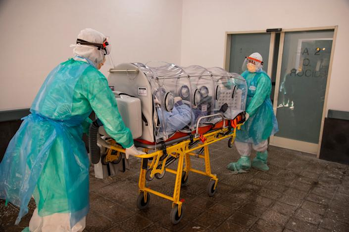 Nurses transport a COVID-19 patient in a biological containment stretcher in the Da Procida Hospital in Salerno, Italy, in April.