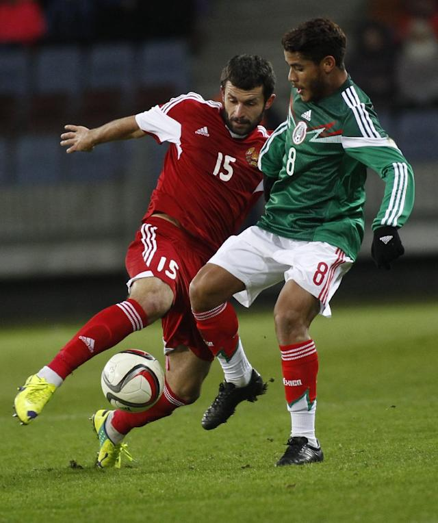 Mexico's Jonathan dos Santos, right, in action against Belarus' Sergei Kislyak during their international friendly soccer at Borisov-Arena stadium in Borisov, Belarus, Tuesday, Nov. 18, 2014. (AP Photo/Sergei Grits)