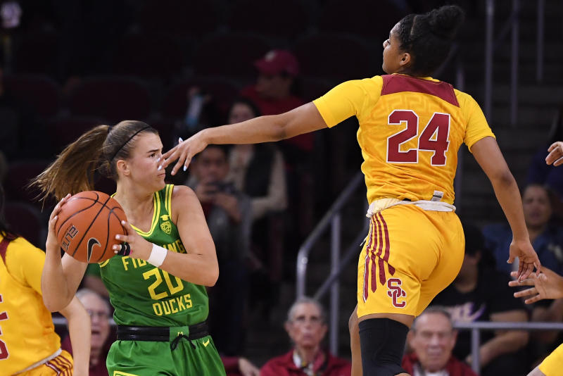 Oregon guard Sabrina Ionescu, left, tries to pass the ball while under pressure from Southern California guard Desiree Caldwell during the first half of an NCAA college basketball game Sunday, Feb. 16, 2020, in Los Angeles. (AP Photo/Mark J. Terrill)