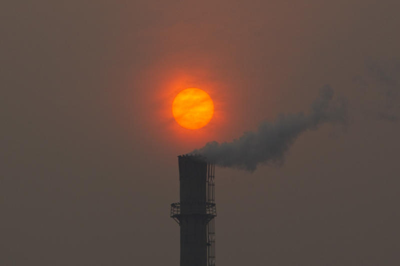 FILE- Smoke billows from a chimney of a heating plant as the sun sets in Beijing in this file photo dated Monday, Feb. 13, 2012.  U.N. climate talks being held in Bonn, Germany, are in gridlock Thursday May 24, 2012, as a rift between rich and poor countries risked undoing some of the advances made last year in the two-decade-long effort to control carbon emissions from fast-growing economies like China and India as well as developed industrialized nations that scientists say are overheating the planet.(AP Photo/Alexander F. Yuan, File)