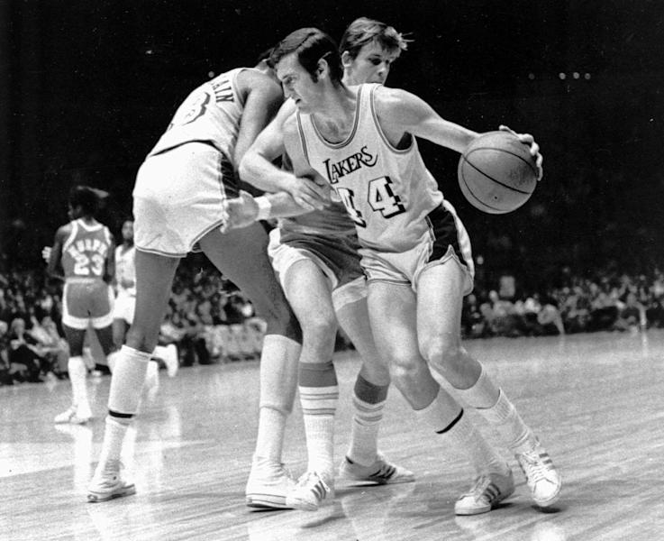 FILE - Los Angeles Lakers' Jerry West (14) is fouled as he tries to get around Houston Rockets' John Vallely after teammate Wilt Chamberlain set screen in game at the Forum in Inglewood, Calif., in this Dec. 27, 1971 file photo. The Lakers went on to their 28th straight win, beating the Rockets 137-115. (AP Photo, File)