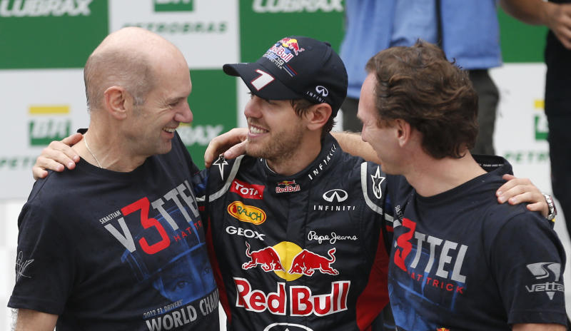 Red Bull driver Sebastian Vettel of Germany, center, celebrates with Red Bull's Technical Chief Adrian Newey, left, and Team Principal Christian Horner, right, after the Brazil's Formula One Grand Prix at the Interlagos race track in Sao Paulo, Brazil, Sunday, Nov. 25, 2012. Vettel overcame a first-lap crash to clinch his third straight Formula One championship title on Sunday, finishing sixth in an incident-filled Brazilian Grand Prix won by Jenson Button under pouring rain.(AP Photo/Victor R. Caivano)