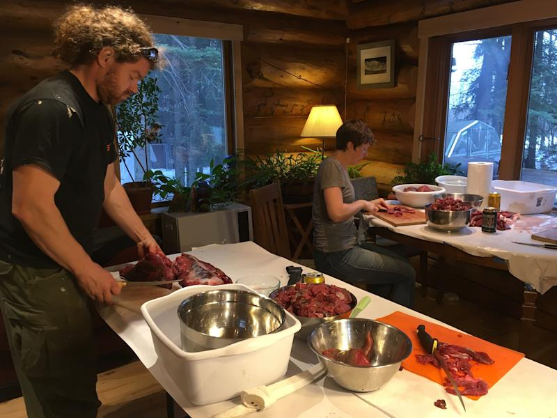 Joanna Young, who took this photo of friends Andrew Cyr (left) and Stephanie O'Daly harvesting roadkill moose meat, was a vegan when she moved to Alaska in 2010. Now Young eats roadkill meat regulary.