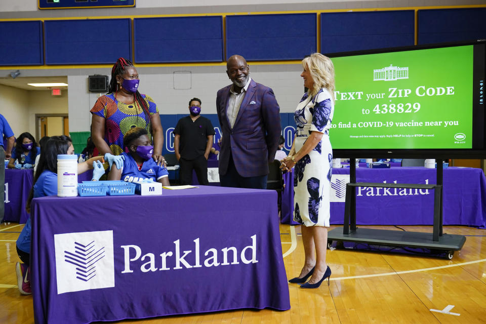 First lady Jill Biden and former Dallas Cowboy and Football Hall of Famer Emmitt Smith tour a vaccination site at Emmett J. Conrad High School in Dallas, Tuesday, June 29, 2021. (AP Photo/Carolyn Kaster, Pool)