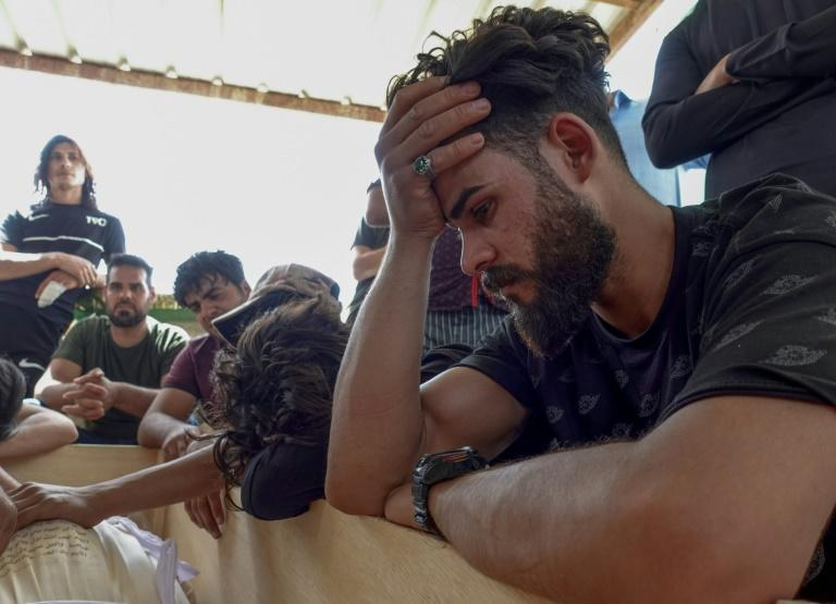 Iraqis mourn relatives killed in a pre-dawn fire that ripped through a Baghdad Covid-19 hospital claiming 82 lives with many victims suffocated or burned in the smoke and flames