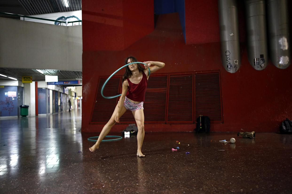 Stav Pinto uses a hula hoop as she practices her acrobatic skills during a weekly informal circus community meeting at the Central Bus Station on July 1. Pinto employs her circus talents to teach life skills to special-needs children. (Photo: Corinna Kern/Reuters)