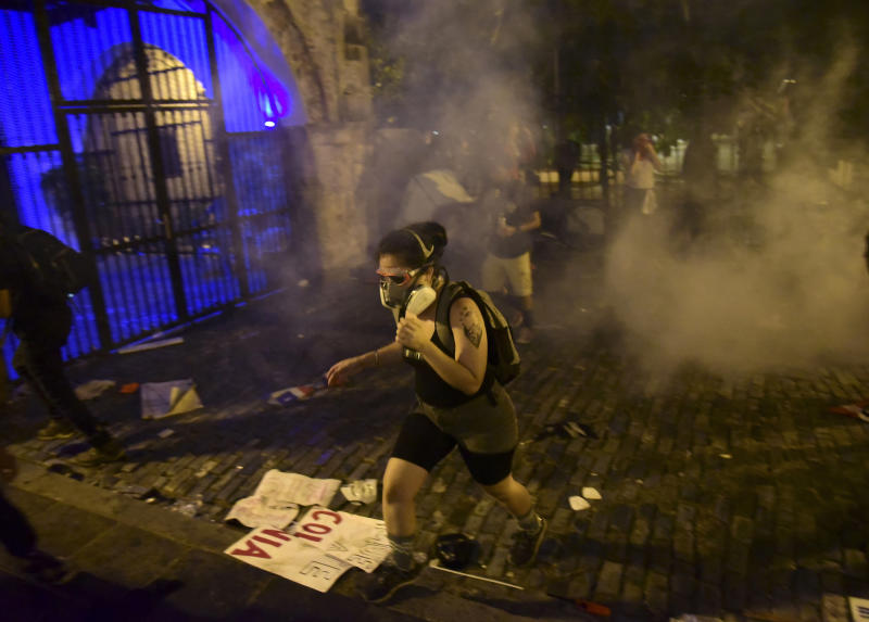Demonstrators affected by tear gas thrown by the police run during clashes near the executive mansion demanding the resignation of Gov. Ricardo Rossello, in San Juan, Puerto Rico, Wednesday, July 17, 2019. (Photo: Carlos Giusti/AP)