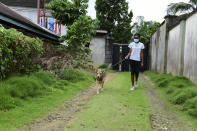 In this photo taken on Wednesday, Oct. 14, 2020, Dodeye Ewa, 16 year old walk with a dog outside her family compound in Calabar, Nigeria. The third child is bothered by President Donald Trump's rhetoric and his policies toward international students, most recently one announced Friday that limits their stays in the U.S. to two or four years with uncertainty about whether their visas will be extended. (AP Photo/Daniel H Williams )