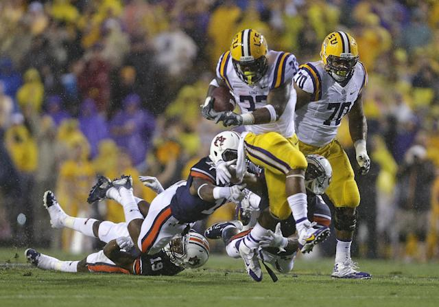 LSU running back Jeremy Hill (33) breaks past Auburn defensive backs Joshua Holsey and Ryan White (19) on a touchdown carry in the first half of an NCAA college football game in Baton Rouge, La., Saturday, Sept. 21, 2013. (AP Photo/Gerald Herbert)