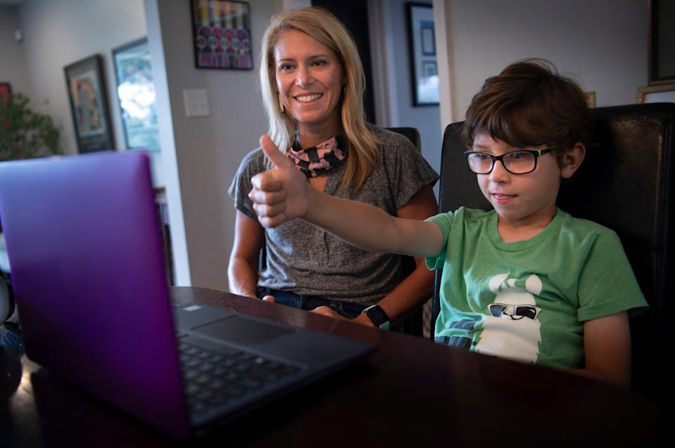 Heather Powell's son, Hawkes, gives a thumbs up as they connect via a laptop and a group chat application to his first grade teacher at Glendale Elementary from their home on the first day of school Aug. 4 in Nashville.