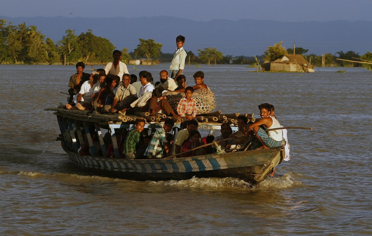 Flood affected villagers crowd a boat in Gagalmari village in Assam state, India, Monday, July 2, 2012. The floods from monsoon rains in northeastern India killed dozens of people, with more than 2,000 villages inundated as rivers breached their banks, an official said Sunday. (AP Photo/Anupam Nath)