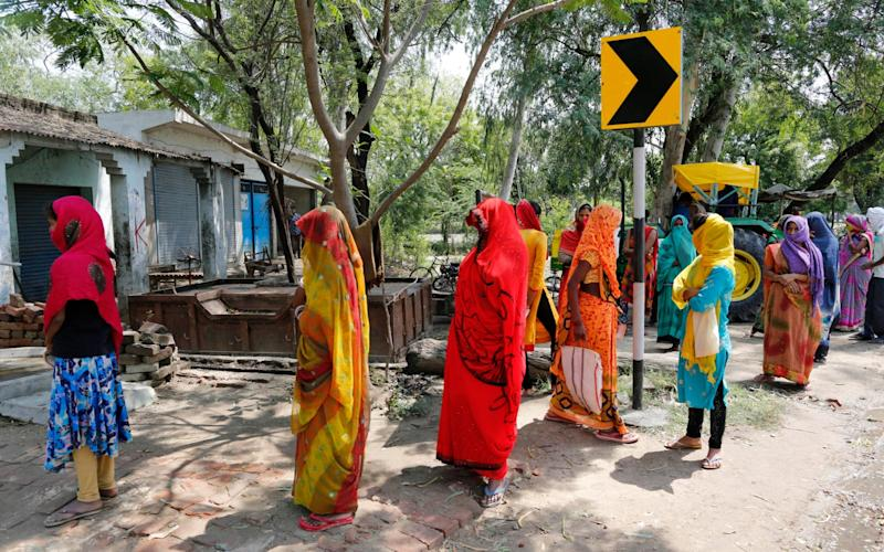 Indian women queue for relief money - Rajesh Kumar Singh/AP