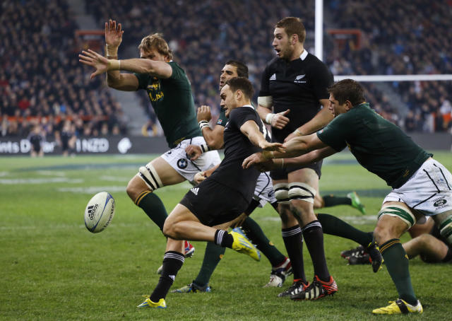 Israel Dagg of New Zealand's All Blacks clears the ball as Andries Bekker of South Africa's Springboks (L) attempts to smother during their Rugby Championship test match in Dunedin September 15, 2012. REUTERS/Anthony Phelps (NEW ZEALAND - Tags: SPORT RUGBY TPX IMAGES OF THE DAY)