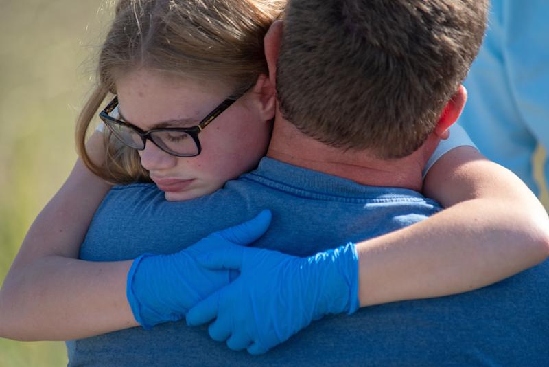 Staff and students comfort each other outside Noblesville West Middle School after a shooting at the school.