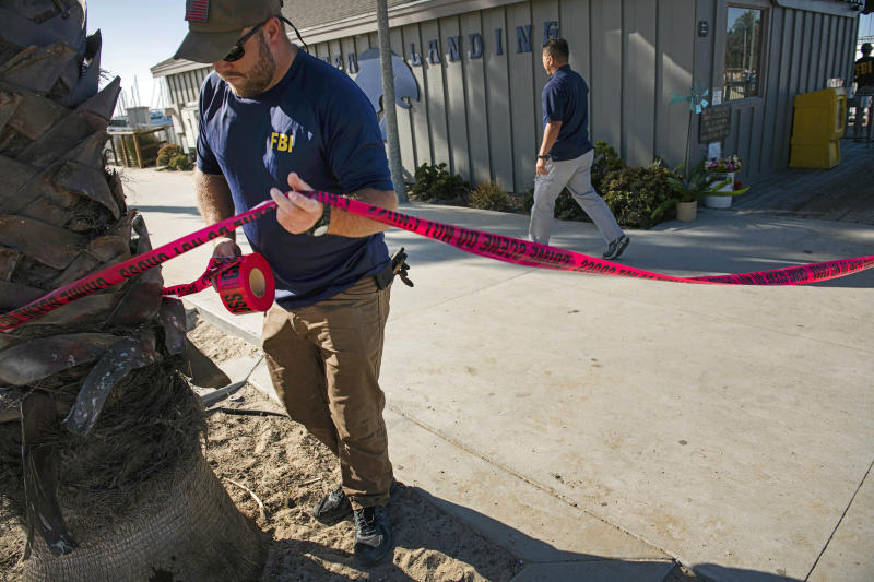 FILE - In this Sept. 8, 2019 file photo, FBI agents set a perimeter around the Truth Aquatics office, the California company that owned the scuba diving boat that caught fire and killed 34 people last week, as authorities issue a search warrant for the company and the sister vessels of the Conception dive boat on the Santa Barbara Harbor in Santa Barbara, Calif. Authorities conducting a criminal investigation into the deadly scuba diving boat fire plan to interview previous patrons of the boat company to determine what kind of safety information they were provided during trips, a law enforcement source said. (AP Photo/Christian Monterrosa, File)