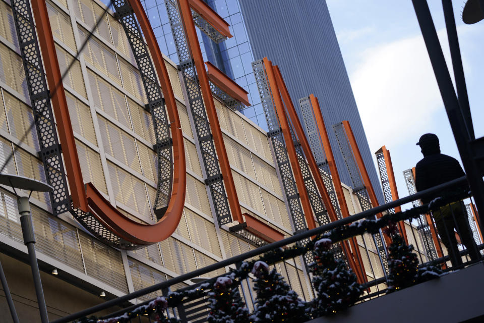 """A shopper pauses to look at a sign spelling out the word """"Denver"""" while in search of after-Christmas bargains in shops in the Denver Pavilions Tuesday, Dec. 29, 2020, in downtown Denver. (AP Photo/David Zalubowski)"""
