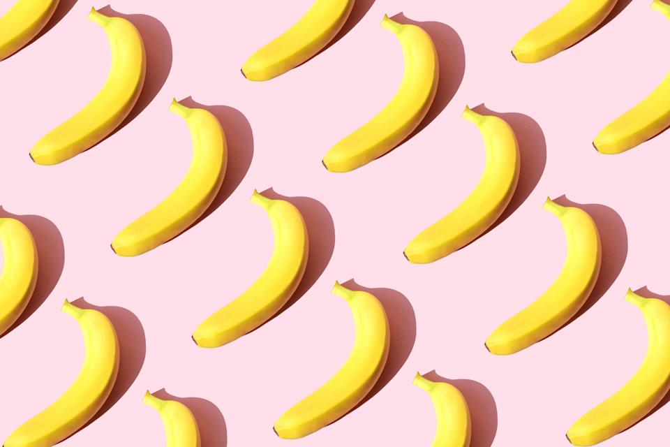 Several bananas arranged neatly in rows on a solid background