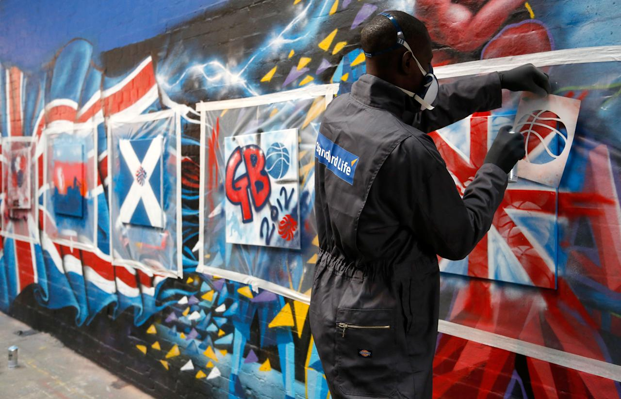 MANCHESTER, ENGLAND - JULY 16: Eric Boateng of the Standard Life Great Britain Men's Basketball team paints a graffiti canvas during a players day at Unity Radio HQ, on July 16, 2012 in Manchester, England. (Photo by Paul Thomas /Getty Images for Standard Life)