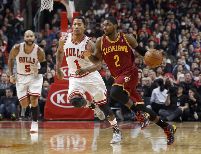 Cleveland Cavaliers guard Kyrie Irving (2) brings the ball up court as Chicago Bulls guard Derrick Rose (1) defends during the first half of an NBA basketball game Monday, Nov. 11, 2013, in Chicago. (AP Photo/Charles Rex Arbogast)