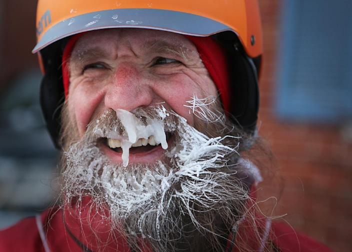 """In a Feb.19, 2014 photo, Fraser Cunningham, 56, a General Electric engineer, arrives home in Madeira, Ohio, with ice that has formed on his beard, which is a product of freezing water vapors produced from breathing. Cunningham calls it his """"chinsulation."""" Cunningham hasn't missed a day biking to and from work for a year and a half. (AP Photo/The Cincinnati Enquirer, Carrie Cochran) MANDATORY CREDIT; NO SALES"""