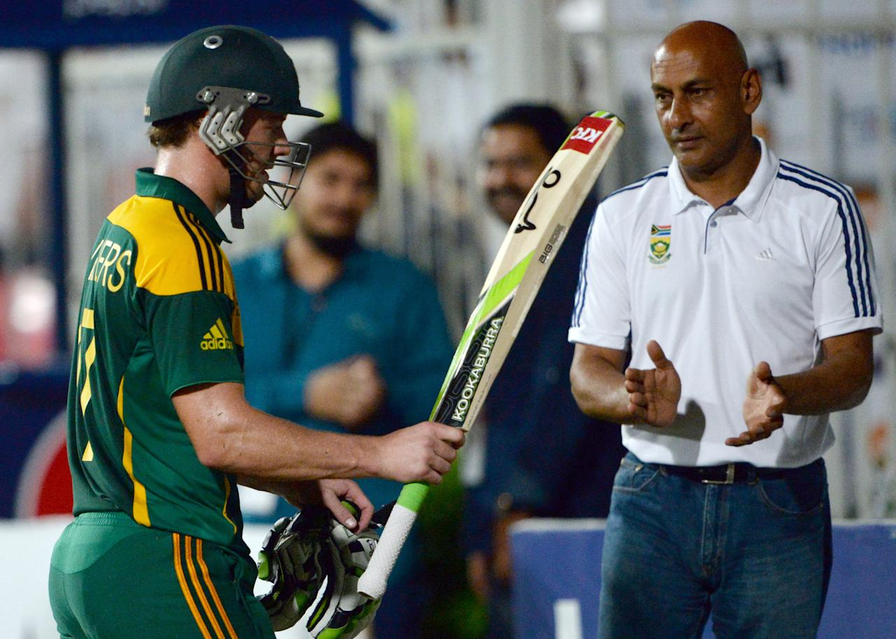 South African captain AB de Villiers (L) wave his bat and leaves the field after making 115 runs during the fifth and final one-day against Pakistan at the Sharjah Cricket Stadium in Sharjah on November 11, 2013. South Africa are winning the five-match series with an unbeatable 3-1 lead. AFP PHOTO/ASIF HASSAN