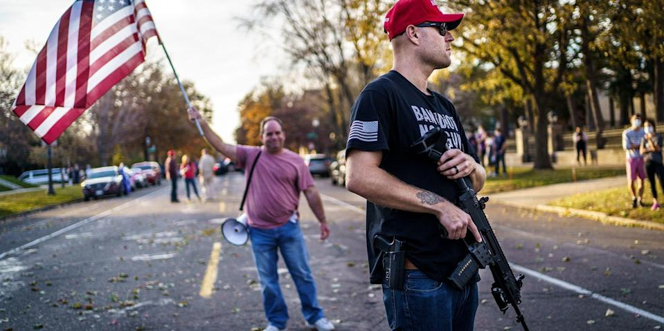 A supporter of US President Donald Trump keeps a hand on his gun during a