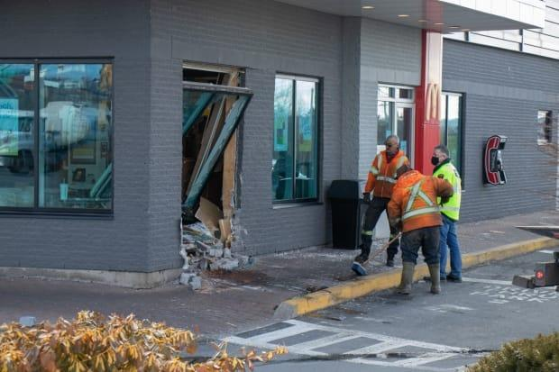 Crews clean up debris after a vehicle smashed into the McDonald's around lunchtime on Wednesday.  (Robert Short/CBC - image credit)