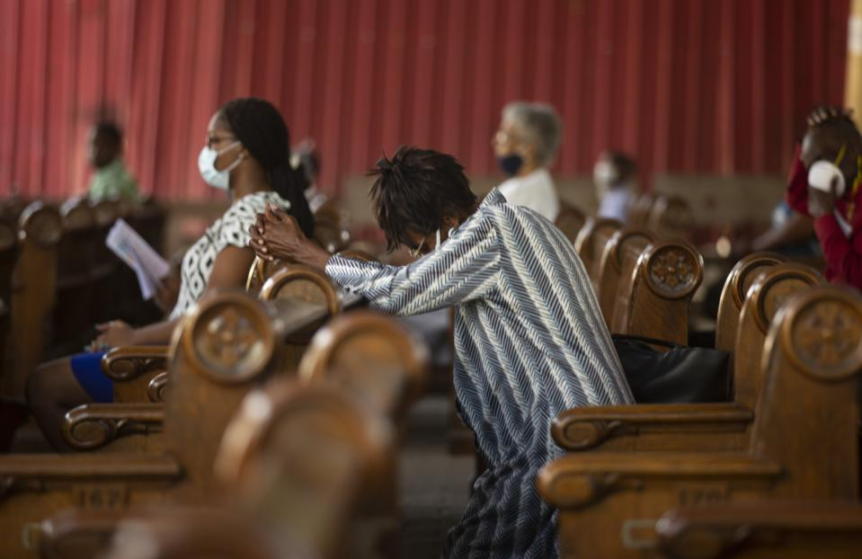A woman prays during Sunday Mass at Sacre-Coeur church, in Port-au-Prince, Sunday, July 11, 2021, four days after President Jovenel Moise was assassinated in his home. (AP Photo/Joseph Odelyn)