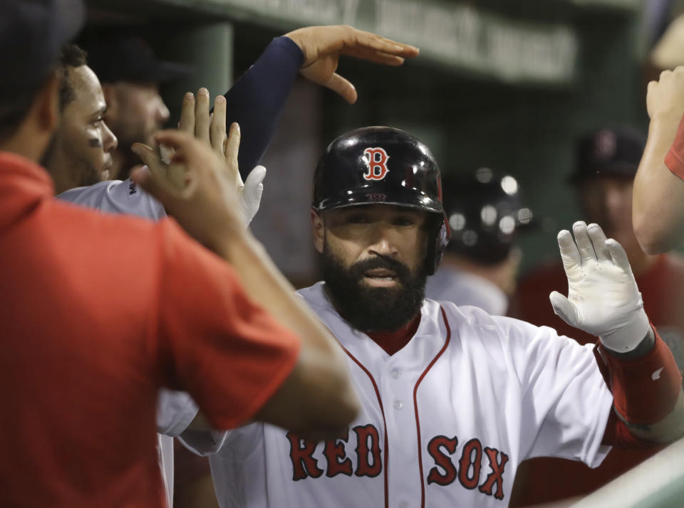 Boston Red Sox's Sandy Leon receives congratulations in the dugout after he hit a solo home run in the fifth inning of the team's baseball game against the Los Angeles Angels at Fenway Park, Thursday, Aug. 8, 2019, in Boston. (AP Photo/Elise Amendola)