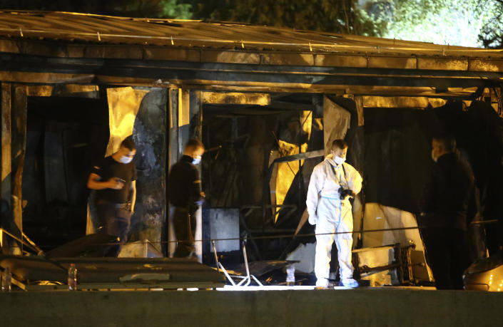 Police officers and forensics investigate the site at a burned out makeshift hospital after a fire in North Macedonia's northwestern city of Tetovo, early Thursday, Sept. 9, 2021. The blaze occurred late Wednesday at the makeshift hospital for COVID-19 patients. (AP Photo/Boris Grdanoski)