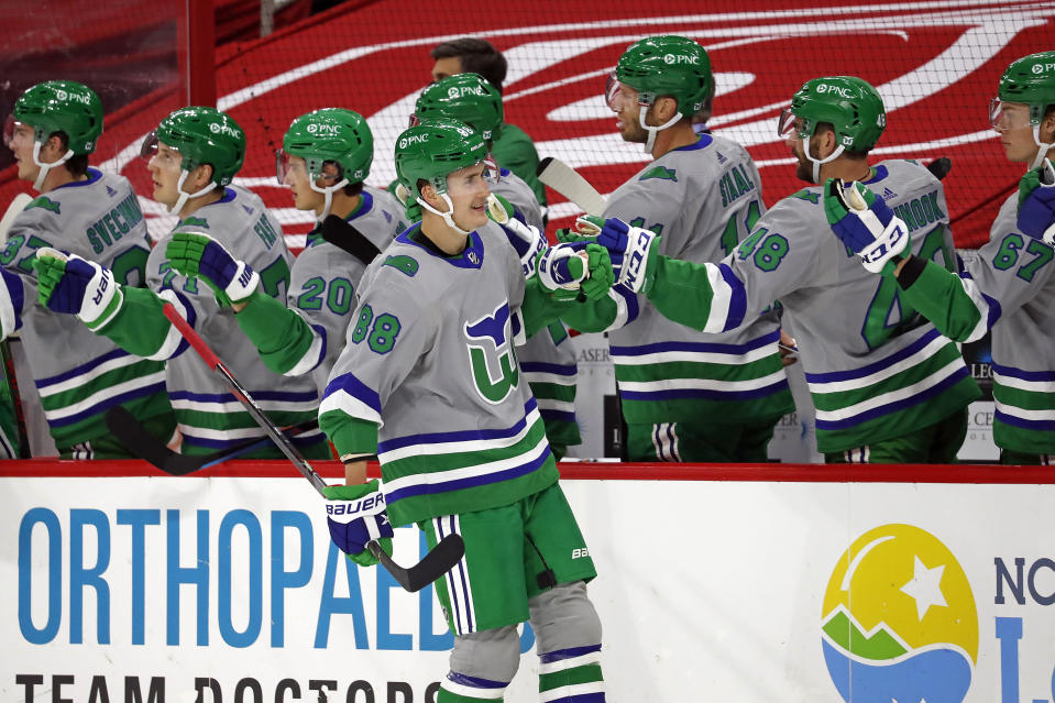 Carolina Hurricanes' Martin Necas (88) is congratulated by teammates on his goal against the Detroit Red Wings during the first period of an NHL hockey game in Raleigh, N.C., Saturday, April 10, 2021. (AP Photo/Karl B DeBlaker)