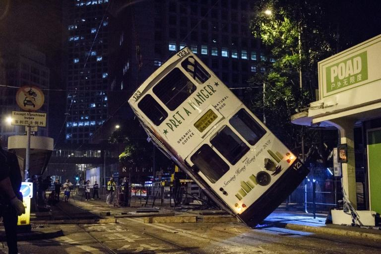 A double-decker Hong Kong tram is lifted by crane after it tipped over on a main road in the city