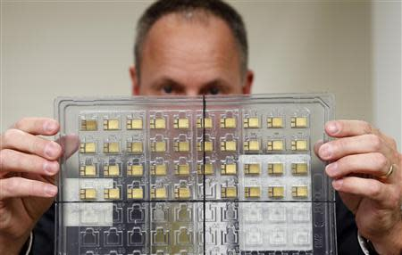 Craig Healy, the U.S. government's chief law enforcement officer for counter-proliferation, displays a set of confiscated American-made radiation-hardened microchips in his office at the Export Enforcement Coordination Center, a joint Homeland Security/FBI/Commerce operation in Northern Virginia November 21, 2013. REUTERS/Kevin Lamarque