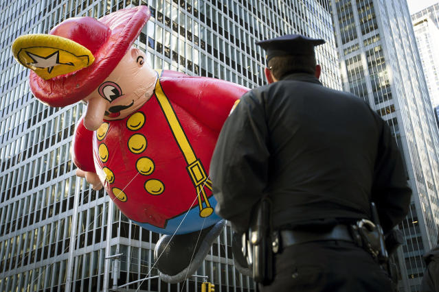 <p>A police officer stands on Sixth Avenue as a giant fireman balloon passes during the 87th Macy's Thanksgiving Day Parade, Nov. 28, 2013, in New York. (Photo: John Minchillo/AP) </p>