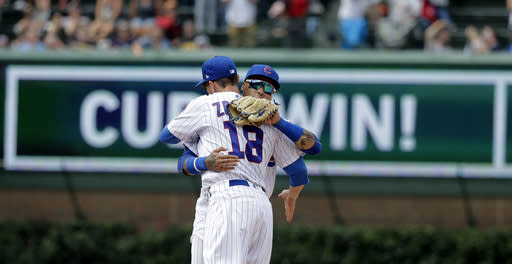 Chicago Cubs' Ben Zobrist (18) and Javier Baez celebrate their win over the St. Louis Cardinals after a baseball game Saturday, July 21, 2018, in Chicago. (AP Photo/Charles Rex Arbogast)